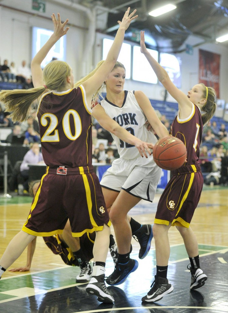 Emily Campbell of York passes to a teammate after driving the lane against Cape Elizabeth defenders, including Hannah Sawyer, 20. York won 47-39 to reach the Western Class B semifinals.