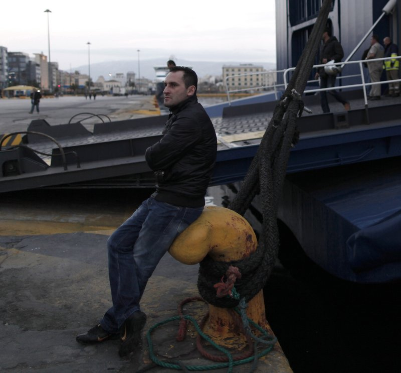 An unpaid striking dock worker sits next to an idle ferry at the port of Piraeus near Athens. Researchers from Greece's largest labor union, the GSEE, say nearly two-thirds of private sector employees no longer get paid regularly, while facing government demands for higher taxes.