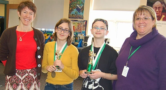 Bonny Eagle Middle School Spelling Bee moderator Ethel Atkinson, left, poses with runner-up Annabel Winterberg, winner Emma Whelchel and bee mistress Krista Poulin.