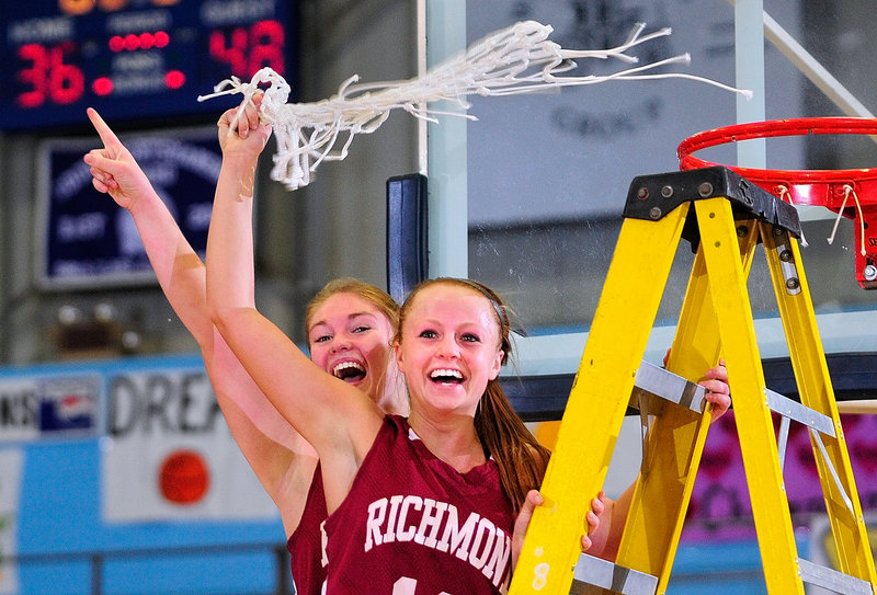 The Richmond captains – Brianna Snedeker, left, and Noell Acord – tear down the net at the Augusta Civic Center after beating Rangeley in Western Class D, 48-36.