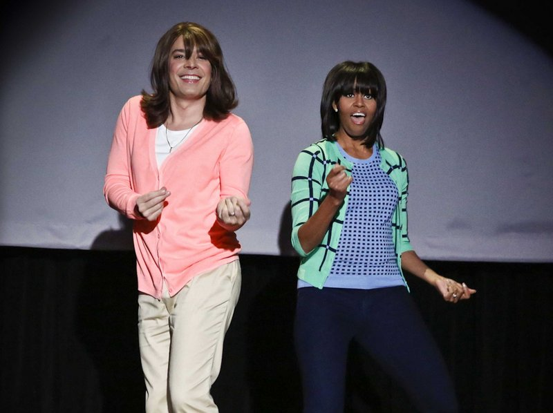 """Host Jimmy Fallon, dressed as a mom, left, dances with first lady Michelle Obama during an appearance on """"Late Night with Jimmy Fallon"""" on Friday."""