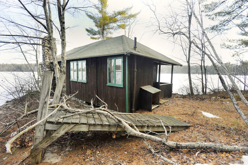 One of the camp's cabins sits on the shore of the lake.
