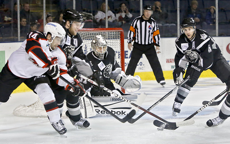 Portland's Chris Conner reaches for the puck as Manchester's Andrew Bodnarchuk, left, and David Kolomatis, right, try to shield goaltender Martin Jones during Sunday's game, won by the Pirates 4-3.