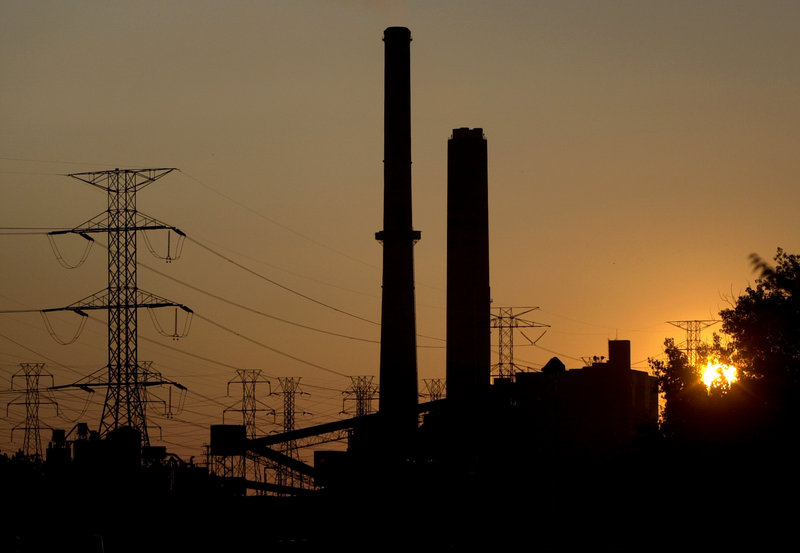 The sun sets behind a coal-fired power plant in Eastlake, Ohio. As part of a settlement with the government and environmental groups, American Electric Power has agreed to stop burning coal at three of its power plants by 2015.