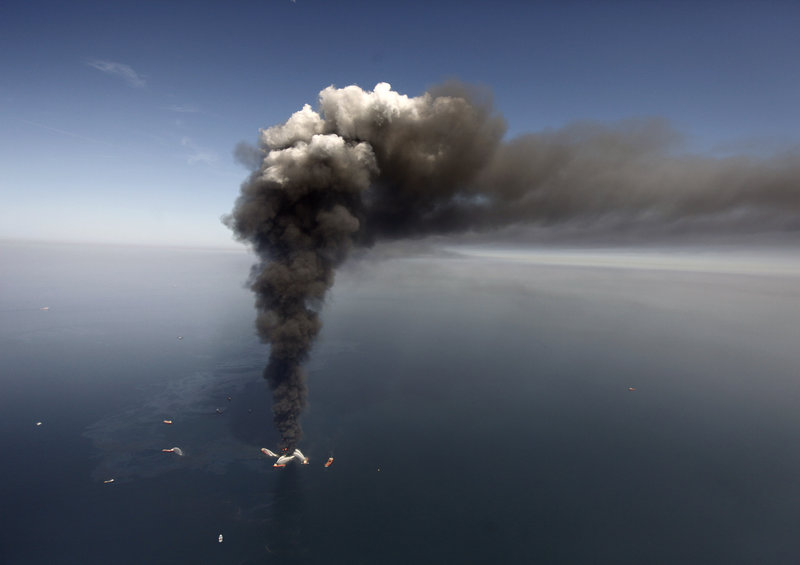 Oil can be seen spreading in the Gulf of Mexico more than 50 miles southeast of Louisiana, as a large plume of smoke rises from fires on BP's Deepwater Horizon offshore oil rig on April 21, 2010.