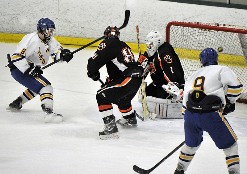 Hugh Grygiel of Falmouth puts the puck past Biddeford goalie Jon Fields, giving the Yachtsmen a 2-0 lead Tuesday night in their Western Class A quarterfinal at Family Ice. Looking to help guard the net for Biddeford is Kerry Crepeau.