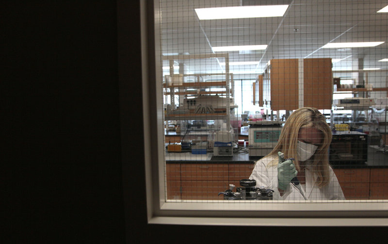An investigator extracts DNA from a sample at the State of California Department of Justice Laboratory in Richmond, Calif.
