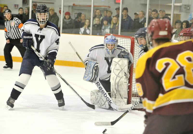 Yarmouth goalie Red DeSmith and Will Porter, left, keep their eyes on the puck as Curtis Guimond of Cape Elizabeth prepares to put a shot on net. Cape Elizabeth will meet Greely in the regional semifinals.
