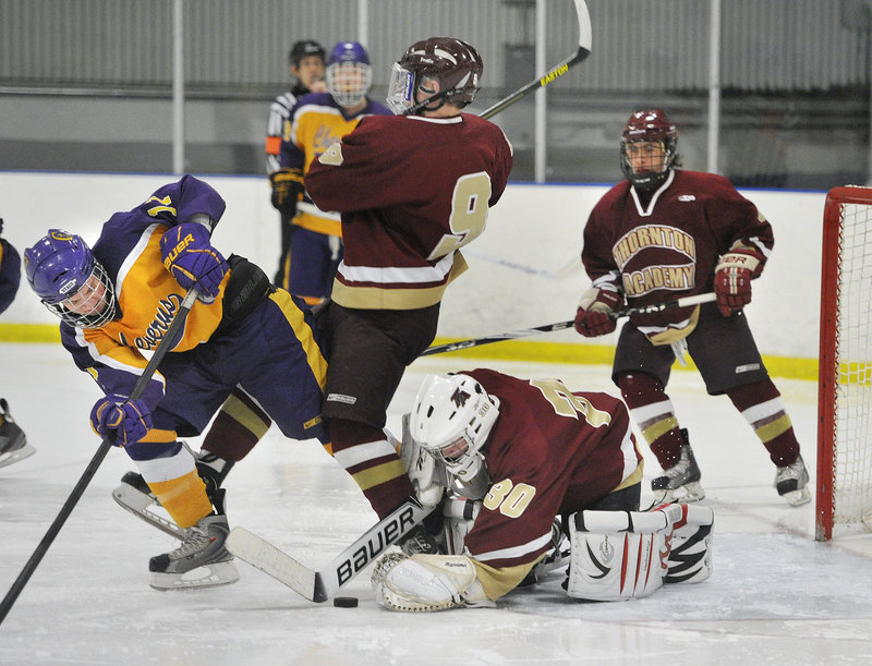 Thornton Academy goalie Andrew Huot dives to cover a loose puck Wednesday night in front of Patrick Sullivan of Cheverus during their Western Class A quarterfinal at the Portland Ice Arena. Cheverus will meet Scarborough in the semifinals Saturday at Lewiston.