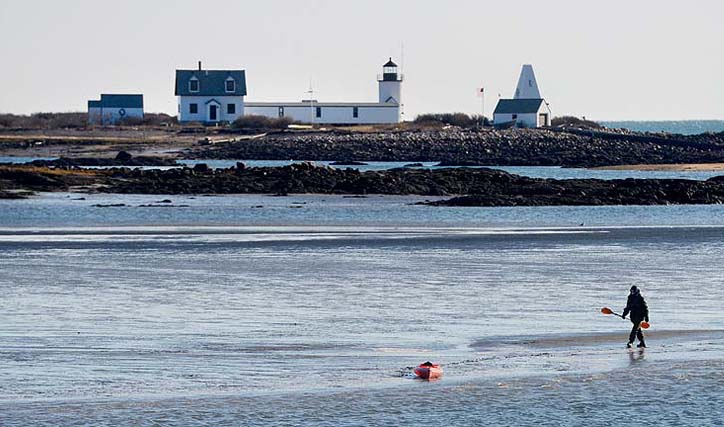 In this file photo, Maine Warden Service Sgt. Tim Spahr searches the water near near Goat Island Lighthouse off Cape Porpoise on Monday, Dec. 24, 2012. The remains of Zachary Wells and Prescott Wright may have washed ashore during the weekend blizzard.