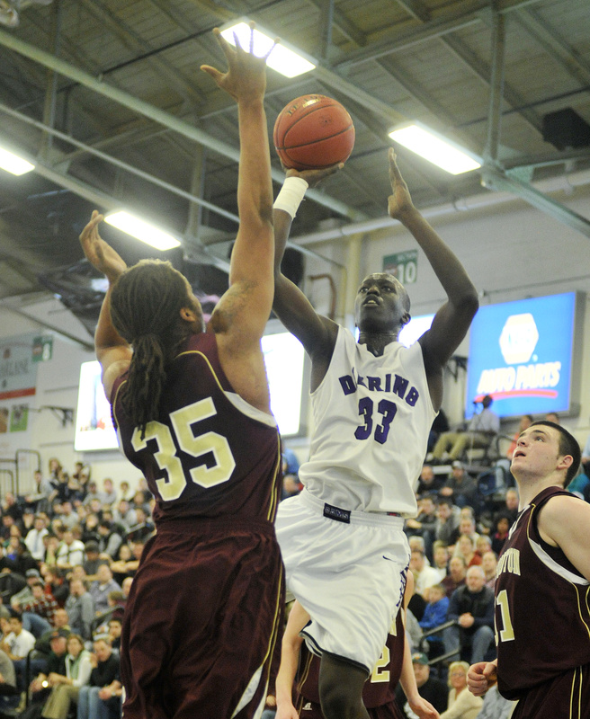 Labson Abwoch of Deering looks to shoot over Malcolm Dopwell of Thornton Academy during their Western Class A quarterfinal at the Portland Expo. Seventh-seeded Thornton upset the No. 2 Rams in overtime, 49-40.
