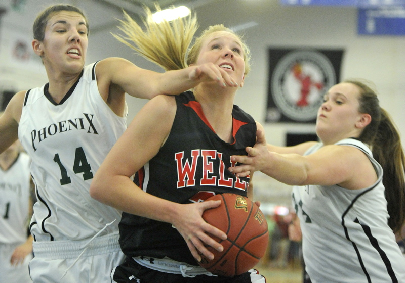 Sophie Lamb of Wells pulls in an offensive rebound between Spruce Mountain's Samantha Richards, left, and Emily Keene.