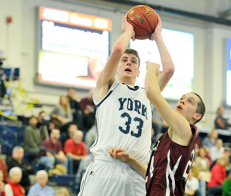 Hayden Webster of York puts up a shot over Greely's Connor Hanley in Saturday's Western Class B boys' basketball quarterfinal at the Portland Expo. Webster scored 13 points in York's 64-38 win.