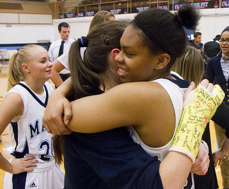 University of Maine junior Ashleigh Roberts hugs teammate Milica Mitrovic, wearing the signed cast from her injury in last week's bus crash, after the team played the University of New Hampshire in Orono on Saturday.