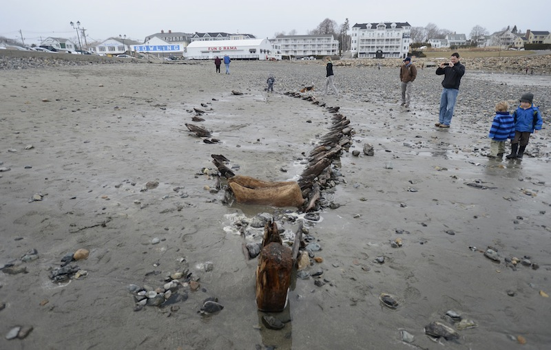 Beachgoers look over a ship's hull Monday that was uncovered at Short Sands Beach in York recently. The hull shows up from time to time when a storm washes away the sand. The hull was last seen following the Patriots Day storm in 2007.