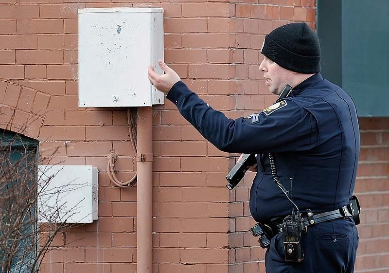A police officer motions to a passerby to get out of the area as police surround the Lafayette Square apartment complex in Portland after gunshots were exchanged on the 6th floor on Friday, March 15, 2013.