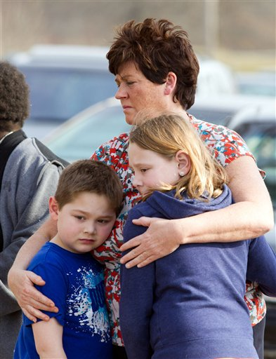 An unidentified woman and her children visit the crash site that claimed the lives of six teens early in the morning on Park Ave. in Warren, Ohio on Sunday, March 10, 2013. (AP Photo/Scott R. Galvin)