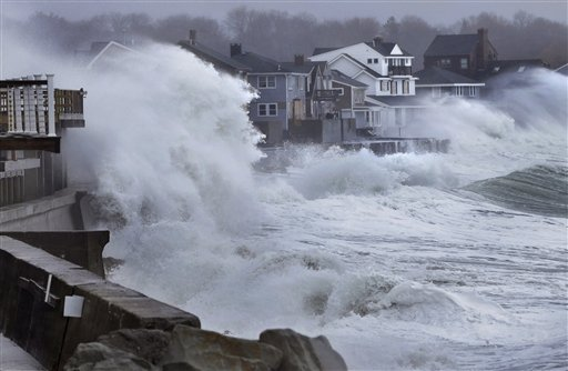 Ocean waves crash over a seawall and into houses along the coast in Scituate, Mass., on Thursday as a nor'easter bringing wind-whipped, wet snow hit Massachusetts.