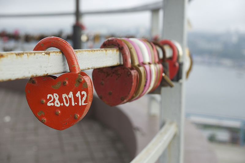 Newlyweds in Vladivostok, Russia, place heart-shaped locks, with the date of their wedding, on a railing on a hillside overlooking the city's harbor.