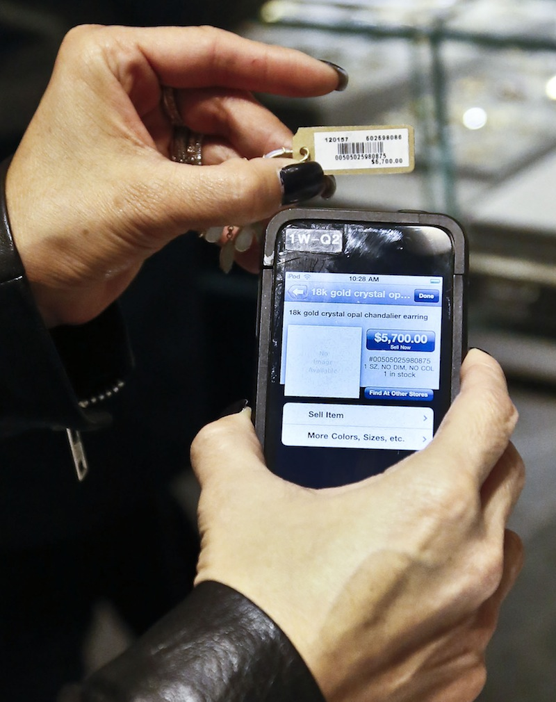 A sales staff member at Barneys New York uses an iPod Touch to help a customer make a purchase. Stores across the country are ditching cash registers and instead having salespeople – and shoppers themselves – check out on smartphones and tablet computers.