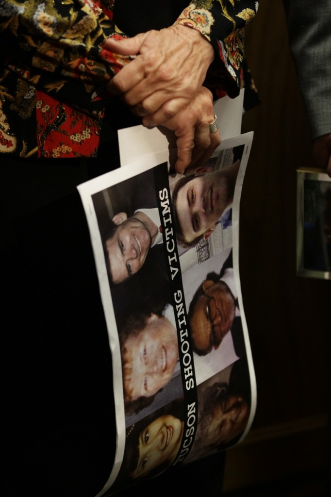 A participant in a news conference in favor of proposed gun control legislation holds a poster picturing victims from the Tucson shooting, inside the Colorado State Capitol, in Denver this month.