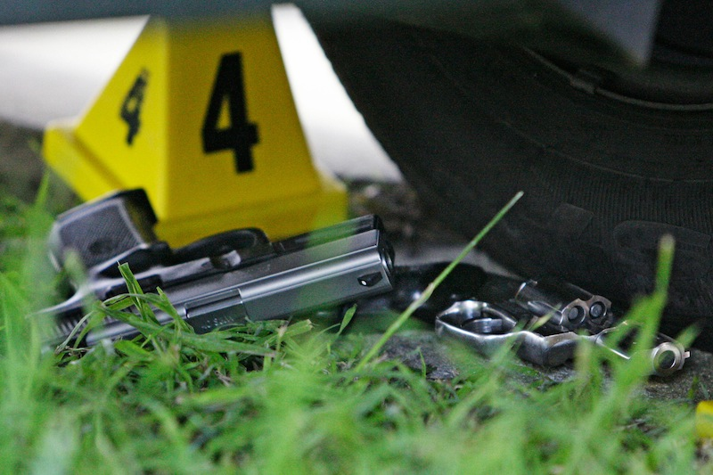In this Tuesday, Feb. 24, 2009 file photo, two guns lie at the scene where five people were shot and two suspects were taken into custody in a shooting incident that happened along the Mardi Gras parade route in New Orleans. States with the most gun control laws have the fewest gun-related deaths, according to a study published Wednesday, March 6, 2013 in the medical journal JAMA Internal Medicine. The study suggests sheer quantity of measures might make a difference. States with the fewest laws and most deaths included Louisiana, Alaska, Kentucky and Oklahoma. (AP Photo/Alex Brandon)