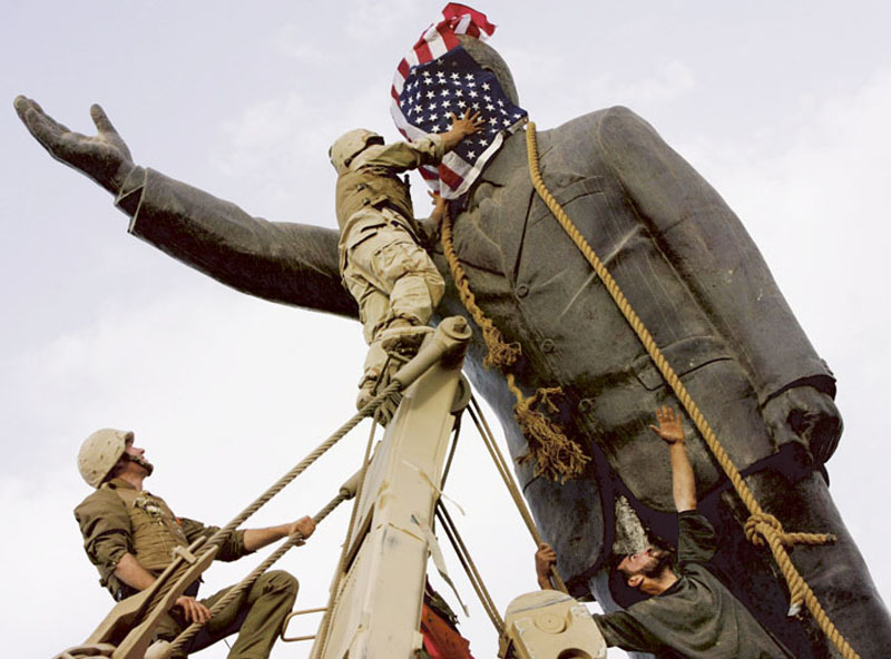 American soldiers cover the face of Baghdad's Saddam Hussein statue with a U.S. flag. Last week's 10th anniversary of the war in Iraq sparked a torrent of coverage and commentary.