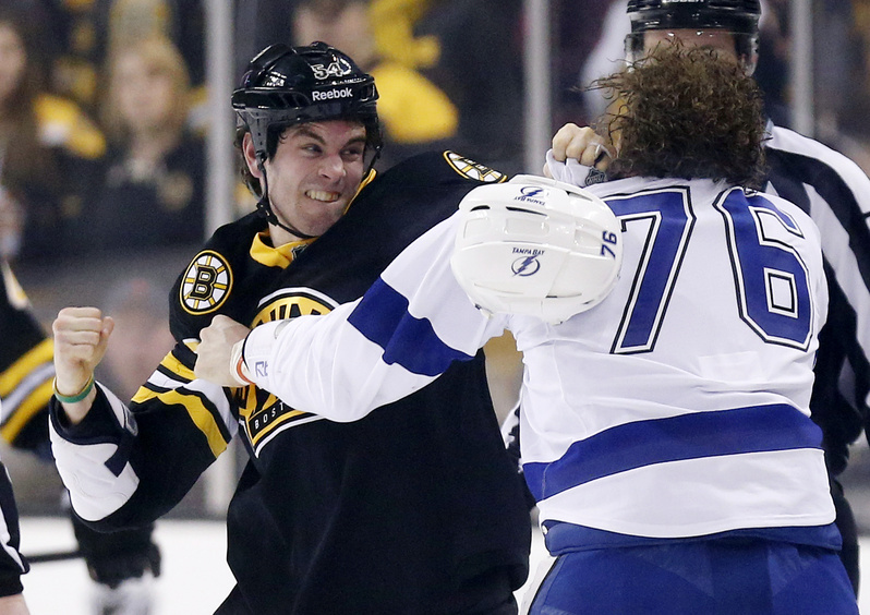 Adam McQuaid, left, of the Bruins and Tampa Bay's Pierre-Cedric Labrie fight during the first period Saturday in Boston.