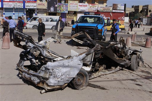 Iraqi security forces inspect the scene of a car bomb attack in the Shiite stronghold of Sadr City, Baghdad on Tuesday. Insurgents unleashed deadly attacks against Shiite areas of Baghdad, killing and wounding scores of people.