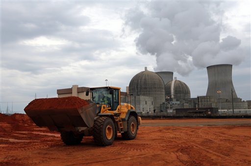 An earth mover works on a new reactor at the Plant Vogtle nuclear power plant in Augusta, Ga., last Dec. 11. One of the plant's existing reactors is shown in the background. Last week, Southern Co. told Georgia regulators that it needed to raise its construction budget for Plant Vogtle by $737 million to $6.85 billion.