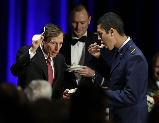 David H. Petraeus, former army general and head of the Central Intelligence Agency, tastes a ceremonial cake presented to him by Hector Sandoval, a member of the USC ROTC program, at the annual dinner for veterans and ROTC students at the University of Southern California, in Los Angeles Tuesday.