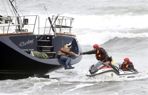 Rescuers attempt to grab a woman off the back of the 82-foot-long sailboat, the Darling, stuck in the surf off Pacifica, Calif., on Monday.