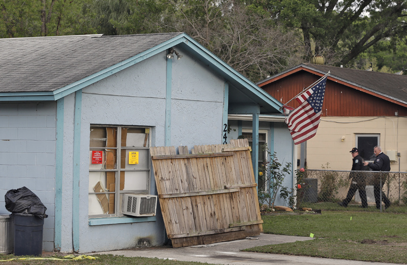 Hillsborough County, Fla., firefighters walk near the front of a home on Saturday where a sinkhole opened up underneath a bedroom late Thursday evening and swallowed a man in Seffner, Fla. Jeff Bush, 37, was in his bedroom Thursday night when the earth opened and took him and everything else in his room. Five other people were in the house but managed to escape unharmed.