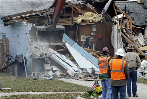 Demolition experts watch as the home of Jeff Bush, 37, is destroyed Sunday in Seffner, Fla. The 20-foot-wide opening of the sinkhole was almost covered by the house, and rescuers said there were no signs of life since the hole opened Thursday night.