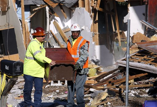 Demolition experts remove a piece of furniture from the home of Jeff Bush, 37, on Monday in Seffner, Fla.