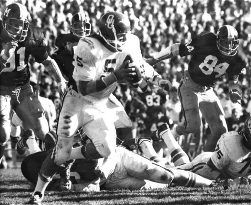In this Nov. 15, 1975, photo, University of Oklahoma quarterback Steven Davis (5) sweeps for a 15-yard gain against Missouri in Columbia, Mo. The starting quarterback for Oklahoma's national championship teams in 1974 and 1975 was one of two men killed when a small plane slammed into a house in northern Indiana.