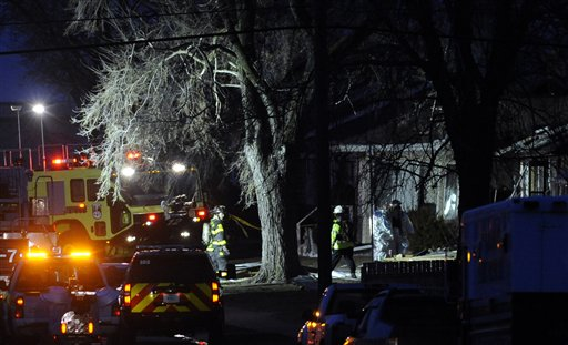South Bend police and fire officials examine a home where a plane crashed near the South Bend Regional Airport on Sunday. The private jet struck three homes, authorities and witnesses said.