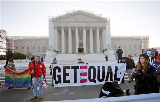 Demonstrators stand outside the Supreme Court in Washington on Tuesday.