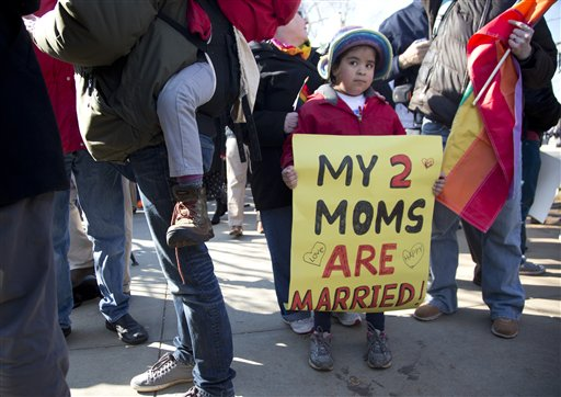 Gabriela Fore, 6, of Upper Darby Pa., holds a sign with her moms in front of the Supreme Court in Washington on Wednesday as the court heard arguments on the constitutionality of the Defense of Marriage Act.
