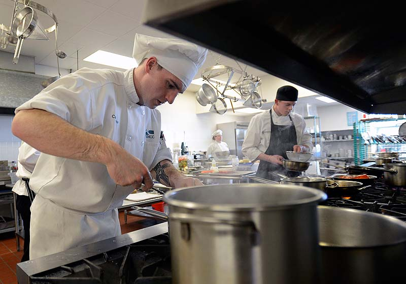Casey Taylor 19, of Kenenbunk, a student at SMMC, prepares a meal during the Chaine des Rotisseurs' Jeunes Chefs Rotisseur Competition at Southern Maine Community College on Sunday. Competing to the right is Andrew Coen 22, of Boston.