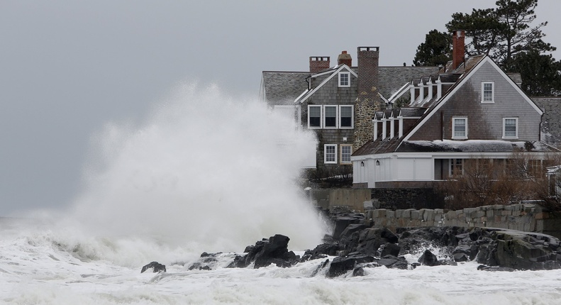 A waves crashes into a house along the shore in Kennebunk in May.