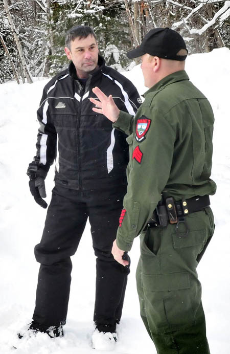 Joseph Paul of Massachusetts speaks with a game warden after bringing missing skier Nicholas Joy out from the Caribou Pond trail near Sugarloaf on Tuesday.