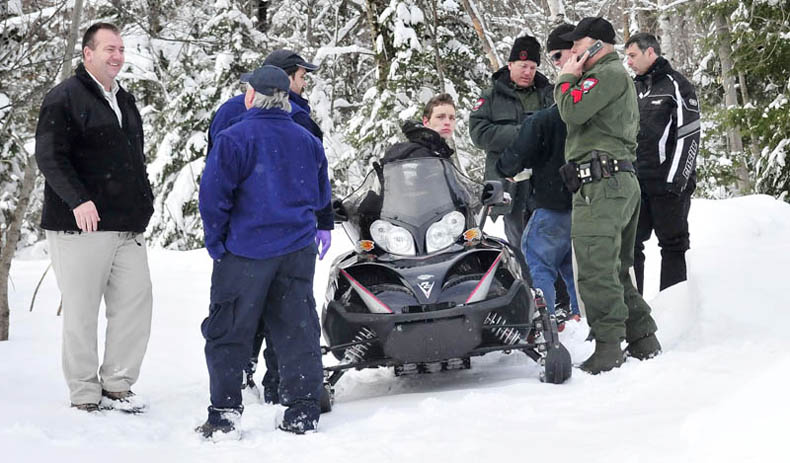 Seventeen-year-old Nicholas Joy is surrounded by game wardens and others who brought him out of the woods Tuesday. At right is Joseph Paul who picked up Joy on the snowmobile and at left is Carrabassett Valley police chief Mark Lopez.