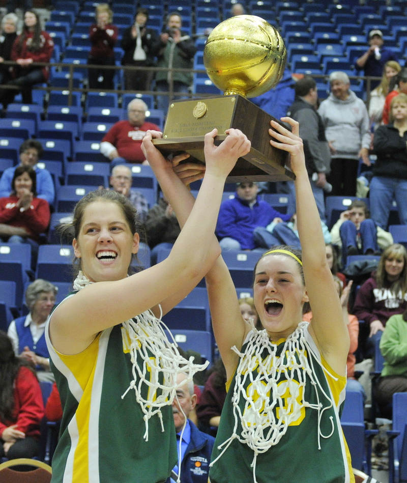 McAuley captains Molly Mack, left, and Allie Clement hold up the Gold Ball after their team won its third straight Class A state championship with a 60-45 victory over Bangor at the Augusta Civic Center.