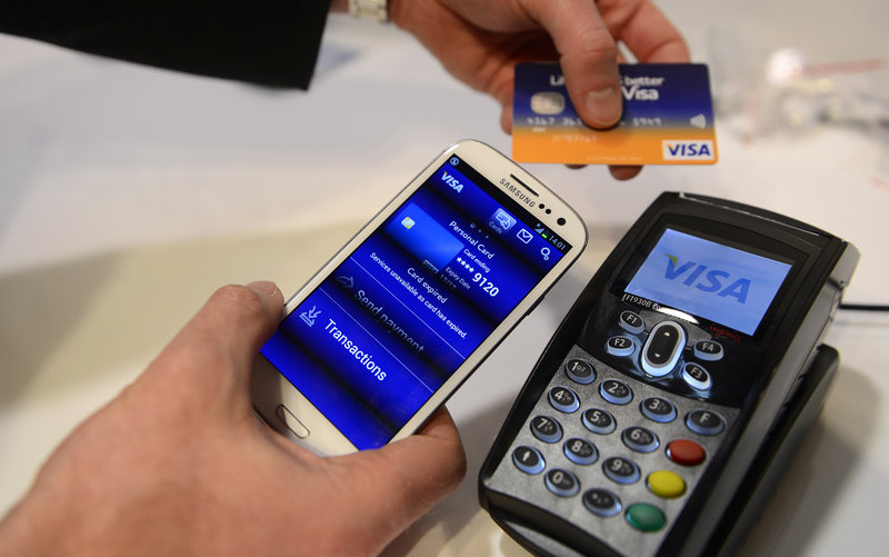 """A Visa cellphone payment system is shown at a trade show this week in Barcelona, Spain. Visa has a deal with Samsung to take charge of the """"secure element"""" in its new cellphone."""