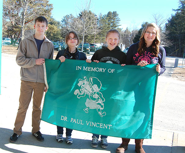 Ronahn Clarke, Sydney Atkinson, Jennifer Turner and Kasey Grant hold Bonny Eagle Middle School's Honor Flag, which was raised to salute their writing achievements in the 2013 Scholastic Art & Writing Awards.