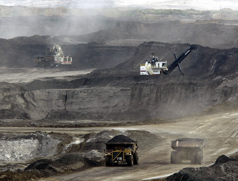 Mining trucks move massive loads of oil-laden sand at the Albian Sands project in Fort McMurray, Alberta, Canada. Tar sands are found in an area almost half the size of Colorado spread across central Alberta.