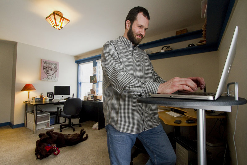 "Mike MacDonald, a software engineer, works at home in Cape Elizabeth on Friday. A telecommuter since 2005 for a company based in California, MacDonald acknowledges, ""sometimes there's no substitute for hashing things out together on a whiteboard and solving a problem."""