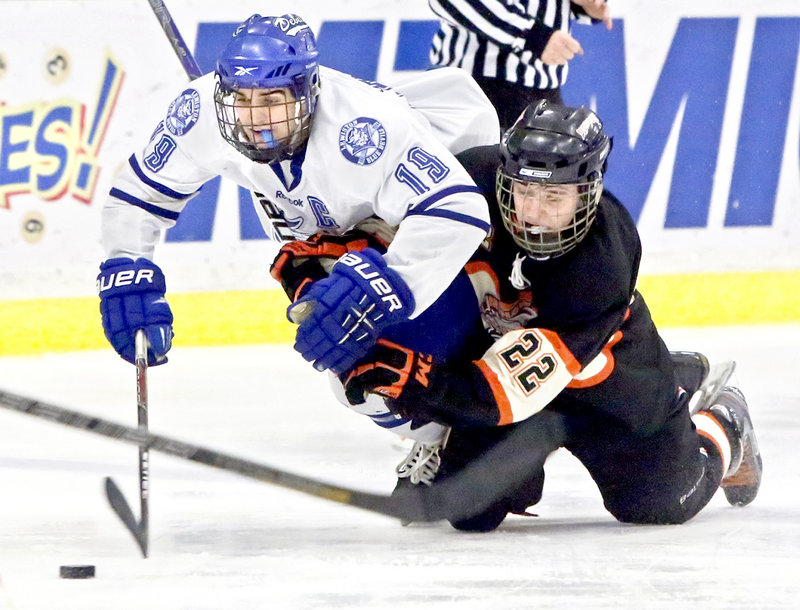 Kyle Lemelin, left, of Lewiston is brought down by Ryan Maciejewski of Brunswick as they chase the puck Saturday during Lewiston's 10-0 victory in an Eastern Class A semifinal.