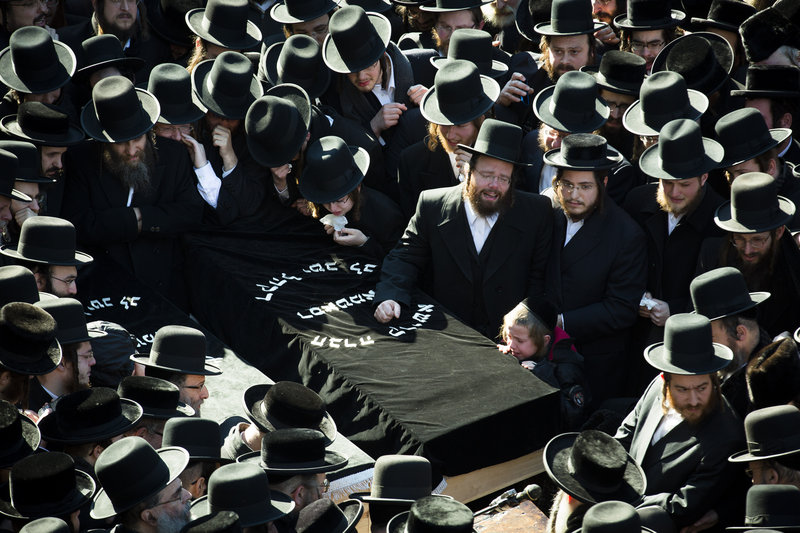 Members of an ultra-orthodox Jewish community gather Sunday for the funeral of two expectant parents who were killed in a car accident that morning in Brooklyn, N.Y.